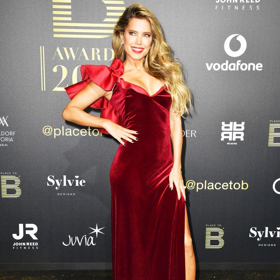 Sylvie Meis trägt ein bodenlanges, figurbetontes Abendkleid aus rotem Samt mit raffinierten Details an der Schulter und im Dekolleté-Bereich. Die elegante Robe stammt von dem Label Winonah.