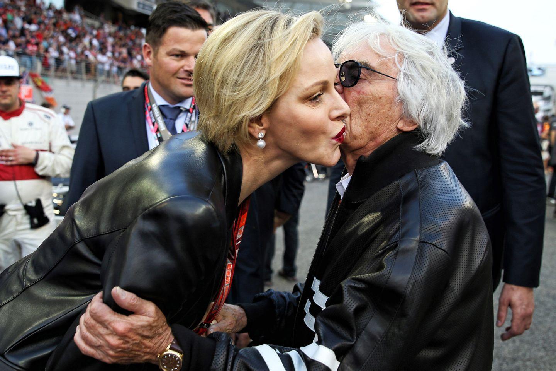 Küsschen, Küsschen... mit ihrem beerenrot glänzenden Lippenstift muss Charlène allerdings aufpassen, dass sie auf der Wange von Formel-1-Chef Bernie Ecclestone keine Spuren hinterlässt.