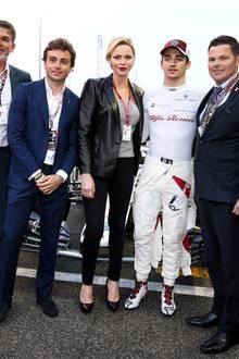 """Formel-1-Fan Fürstin Charlène lässt sich das Rennen in Abu Dhabi nicht entgehen, und nutzt die Chance gleich noch für ein Gruppenfoto mit """"ihrem"""" Alfa Romeo Sauber F1 Team. Mit stylischemLeder-Blazerzu grauem Top und schwarzer Slim-Jeans findet sie dabei wie immer genau die richtige Balancezwischen Eleganz und Sportlichkeit."""