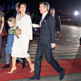 Auch bei der Ankunft des Kronprinzenpaares zeigt sich Mary im Hochzeitsook. Um sich vor der Kälte zu schützen, hat sie sich einen weißen Wollmantel über die Schultern gelegt. Zu dem hellen Outfit kombiniert Mary goldene Schuhe der Marke Gianvito Rossi. Der Blumenstrauß in Marys Händen lässt Mary noch einmal mehr wie eine Braut aussehen.