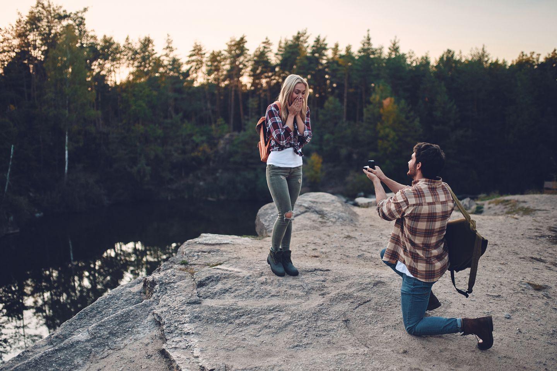 Ein junger Mann geht vor seiner Freundin auf die Knie und macht ihr einen Antrag