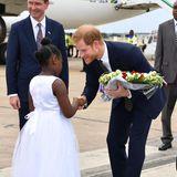 26. November 2018  Bei seiner Ankunft in Sambia wird Prinz Harry von einem einheimischen Mädchen mit Blumen begrüßt.