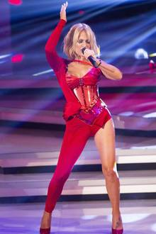 """Trotz des aufwendigen Kostüms scheint Michelle in ihrer Bewegungsfreiheit nicht eingeschränkt zu sein: Ihren Song """"In 80 Küssen um die Welt"""" performt sie mit vollem Körpereinsatz. Während ihr Bühnenoutfit extrem auffällig ist, stylt Michelle ihren lediglichmit leichten Locken. In Sachen Schmuck setzt sie nur auf ein Armband am linken Handgelenk. Durch den Schnitt ihres Einteilers und die roten Pumps istder Blick auf ihr blumiges Fußtattoo frei."""