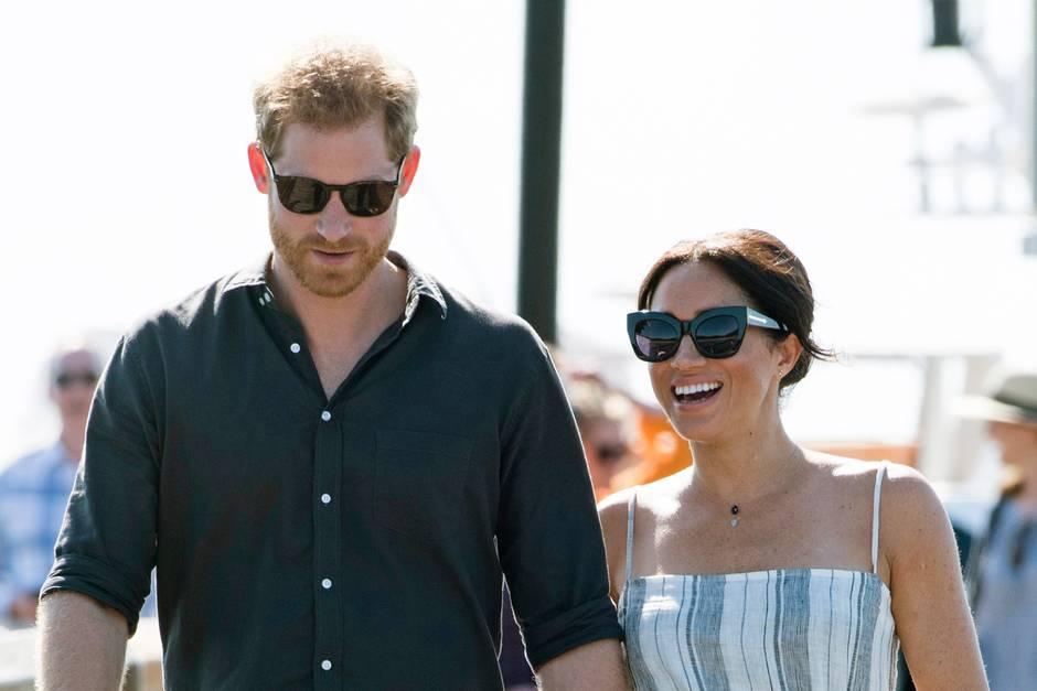 Prinz Harry und Herzogin Meghan flanieren in Australien über eine Strandpromenade.