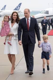 Herzogin Catherine und Prinz William reisten im Juli 2017 mit ihren Kindern nach Polen und Deutschland. Auch in Warschau konnte man ein typisches Bild der Familie Cambridge sehen: Während Kate Charlotte auf dem Arm trägt, läuft George an Williams Hand.