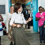 Prinzessin Mary schwingt bei ihrem Besuch im Kibera Slum die Hüften. Ihr Midi-Rock in olivgrün eignet sich perfekt für eine kleine Tanzeinlage. Dazu trägt die Kronprinzessin Dänemarks eine weiße Bluse und lässige Sneaker von Newbalance.