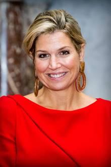 Bei der Verleihung des Erasmuspreises 2018 an die amerikanische Journalistin und Schriftstellerin Barbara Ehrenreich im Königlichen Schloss, Amsterdam zeigt sich KöniginMáxima strahlend schön in einem roten Kleid undauffälligem Ohrschmuck. Die Haare trägt die 48-Jährige zu einem locker-sitzendemDutt.
