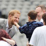 Wie das kitzelt! Prinz Harry bekommt den Bart gekrauelt. Ein kleiner Junge scheint Gefallen an der roten Bartpracht des Prinzen gefunden zu haben.