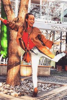 Dieser Look bereitet nicht nur Annemarie gute Laune. Auch wir strahlen beim Anblick ihres Outfits. Zu ihrem dünnen Strickpullover kombiniert sie einen braunen Wildledermantel, passende Booties und eine hellgraue Jeans.