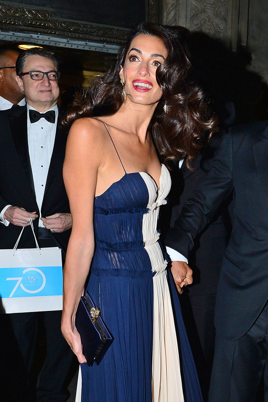 Amal,die gerademit dem UNCA Award ausgezeichnet worden ist,bezaubert im blau-weißen Abendkleid von J.Mendel mit tiefem Ausschnitt, das nicht nur ungewöhnlich sexy ist für die Menschenrechtsanwältin, sondern auch mal wieder ein echtes Luxusteil, mit umgerechnet ca. 5.725 Euro nicht gerade ein Schnäppchen.
