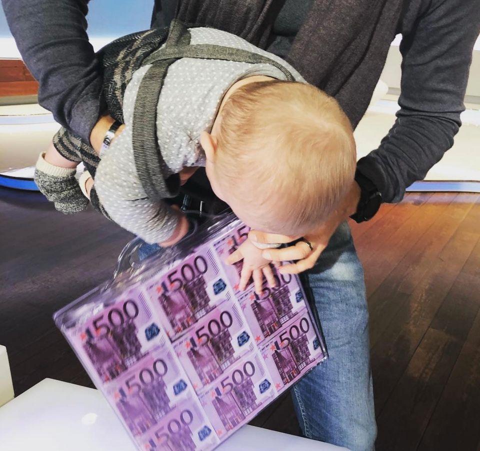 """6. Dezember 2018  Beim Set-Besuch nimmt Mini-C gleich ein wertvolles Requisitin Beschlag. Der kleine Sohn hat es tatsächlich auf den Geldkoffer abgesehen, der eigentlich dem Sieger des Gewinnspiels zusteht. """"Ganz die Mama!"""", witzelt Wayne."""