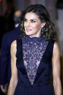 Dieser Ausschnitt kann sich wirklich sehen lassen! Letizia wählt in Madridein dunkelblaues, ärmelloses Kleid mit einem etwas helleren Spitzeneinsatz im Brustbereich. Der v-förmige Einsatz, der fast bis zum Bauchnabel geht, gibt den Blick auf Letizias Dekolleté frei. Ihre Taille betont die spanische Königin mit einem zarten Gürtel mit Schleife. Zu dem aufregenden Kleid kombiniert Letizia lange Ohrringe mit silbernen und blauen Steinen, ihre Haare trägt sie gelockt. In Sachen Make-up hält sich die ehemalige Journalistin zurück und betont ihre Lippen und Augen dezent.