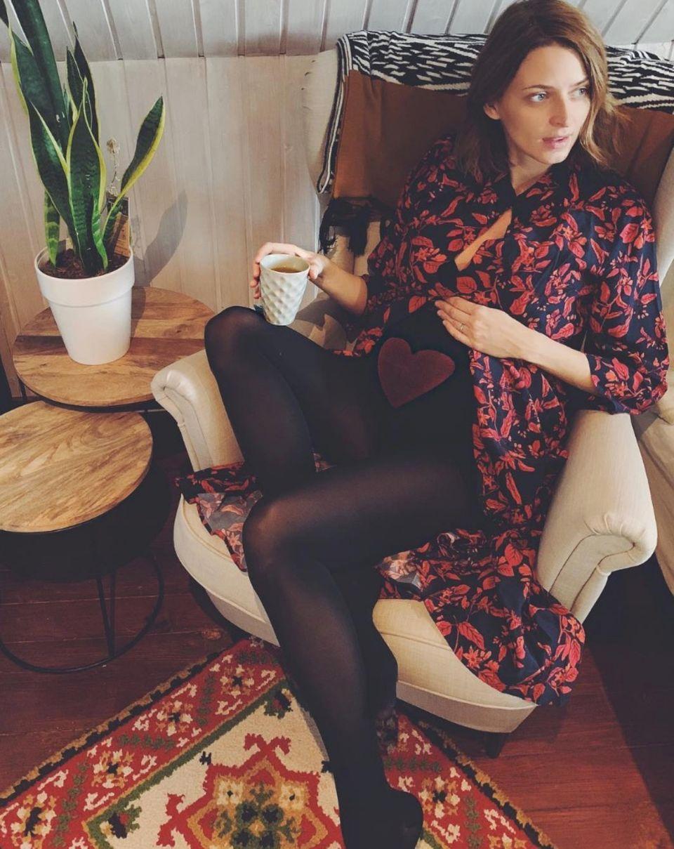 So schön hat Eva Padberg ihre Babykugel noch nie präsentiert. Entspannt trinkt das Modeleinen Tee und streichelt über den wohl bestgestylten Babybauch aller Zeiten:Die Strumpfhose istmit einem großen Herz bedruckt. Sehr süß!  Nikolaus verbringt die Schwangere mit ihrer eigenen Mutter und demwachsenden Bäuchlein. Nächstes Jahr um diese Zeit wird sie das Fest schon mit ihrem Nachwuchs feiern.