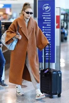Gigi Hadids graue Jogginghose besteht natürlich nicht nur aus alt bekanntem Fließ, sondern aus unempfindlichem Bouclé mit Anteilen aus Wolle, Seide und Cashmere – und das hat seinenPreis: Der Jogger liegt beistolzen 2.100 Euro. Dazu kombiniert das Model Sonnie high-top Sneaker von Chloé im Wert von 600 Euro, einen grauen Rollkragen-Pullover aus Cashmere und einen orangefarbenen Wollmantel im Oversized-Look.