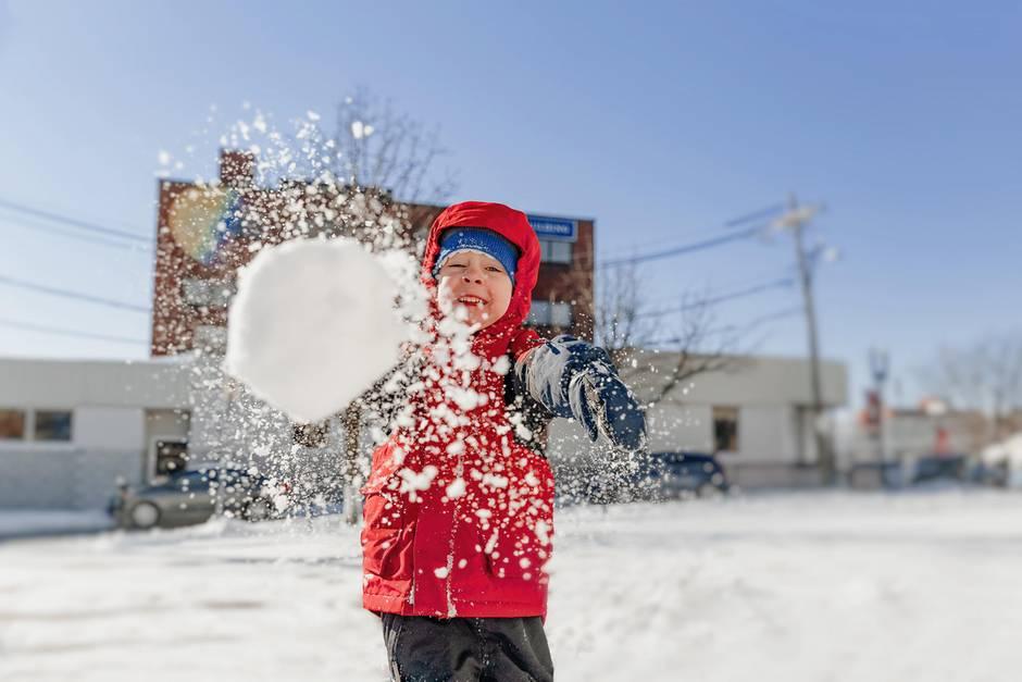 Volle Kraft voraus: Ein Junge setzt zur Schneeballschlacht an