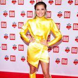"""Bei der """"Ein Herz für Kinder""""-Gala schimmert Sophia Thomallas Kleid nur so im Scheinwerferlicht. Der gelbe Satinstoff scheint förmlich zu leuchten. Die Farbe ist gewagt, doch Sophia kann es tragen!"""