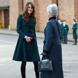 Im November 2012 besucht Herzogin Catherine in einem ähnlichen Modell ihre ehemalige Schule. Auch sie trägt ihr brünettes Haar offen und kombiniert schwarze Wildlederstiefel.