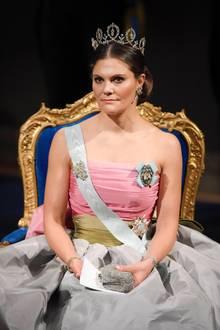 Prinzessin Victoria zeigt in ihrem diesjährigen Nobelpreiskleid die kalte Schulter. Damit ihre Schulterpartie und die muskulösen Arme perfekt in Szene gesetzt werden, trägt sie ihr Haar kunstvoll hochgesteckt. Eine Glitzerclutch macht den glamourösen Look perfekt.
