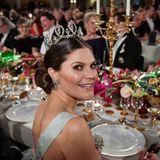 Prinzessin Victoria schenkt dem Fotografen ein letztes Lächeln über die Schulter, bevor sie sich dem festlich gedeckten Tisch zuwendet.