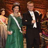 Königin Silvia hat eins ihrer alten Kleider ihrer Tochter Victoria vermacht und trägt an diesem Abend eine dunkelgrüne Spitzenrobe mit nackten Schultern. Sie kommt am Arm vonCarl-Henrik Heldin die Treppen des Stockholmer Rathaus herunter.
