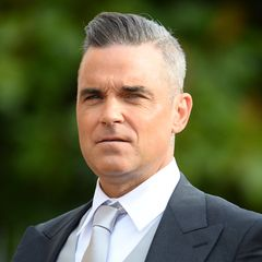 """Robbie Williams etabliertnach dem Aus von Take That als erfolgreicher Solokünstler, der mit 15 Brit-Awards ausgezeichnet wird. Alben wie """"Life Thru a Lens"""" mit der Liebeshymne """"Angels"""" und """"Swing When You're Winning"""" werden zu bahnbrechenden kommerziellen Erfolgen. Als für seine Tour 1,6 Millionen Tickets an einem einzigen Tag verkauft werde, landet der britische Sänger sogar im Guinness-Buch der Rekorde.2010 heiratet erseine Freundin Ayda Field nach vier Jahren Beziehung. Im September 2012 erblickt Töchterchen Theodora """"Teddy"""" Rose das Licht der Welt."""