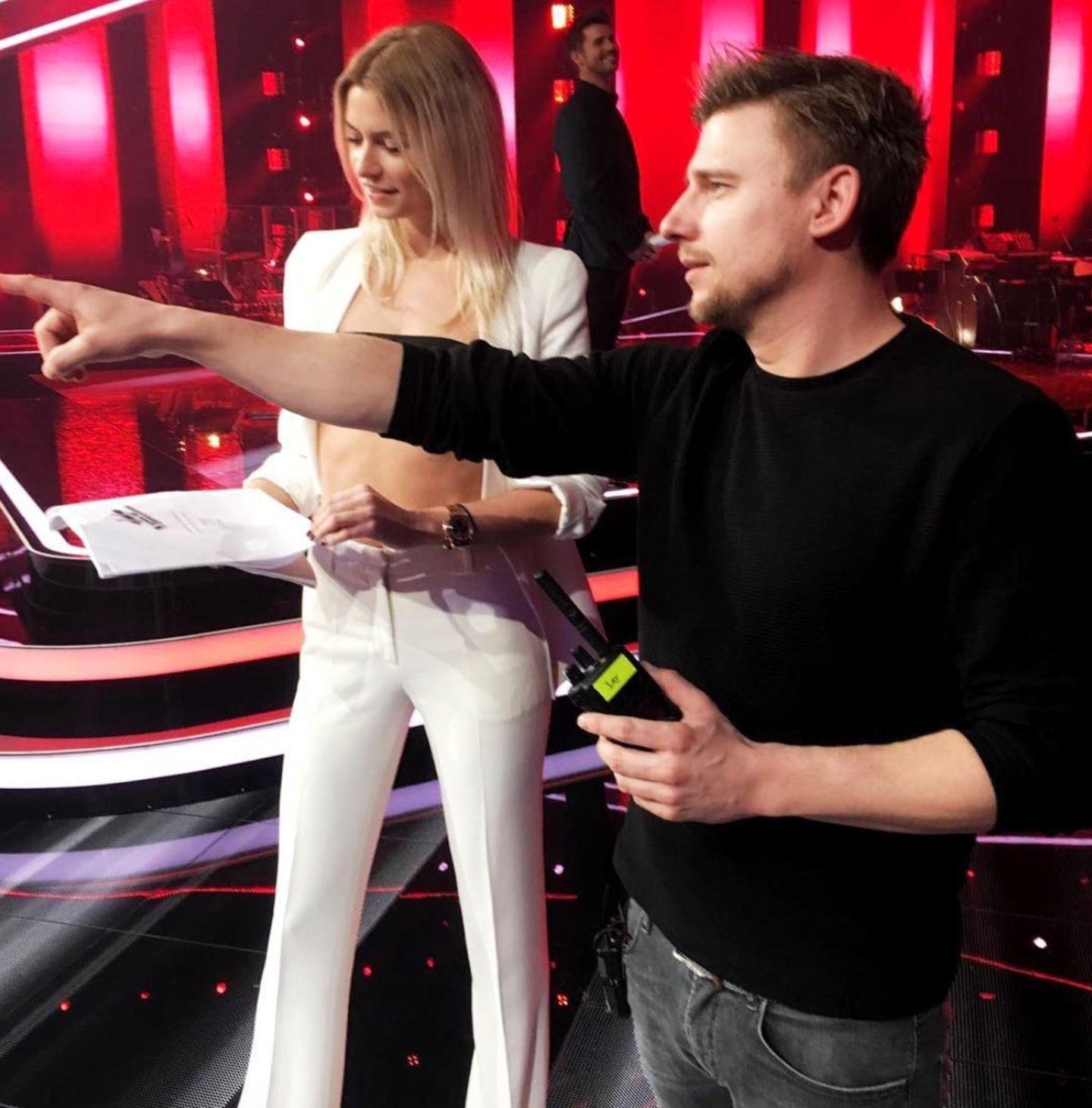 """Lena Gercke postet ein Foto vom Set der Show """"The Voice of Germany"""". Ein Detail verwirrt allerdings: Zeigt sich die ehemalige GNTM-Gewinnerin da gerade oben ohne? Nur der Arm eines Mitarbeiters scheint die Brüste der schönen Blondine zu verdecken.Doch natürlich läuft Lena nicht nackt durch das Studio. Wer genauer hinsieht, erkennt, dass sie ein kurzes, schwarzes Top trägt. So entsteht die optische Täuschung."""