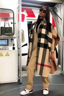 Reisen mit Stil: Supermodel Naomi Campbell fliegt sicherlich nicht Holzklasse und auch ihr Outfit selbstverständlich kein günstiger Wohlfühl-Look vom Discounter. Allein ihr Cape von Burberry kostet rund 1.600 Euro.