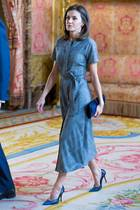 In einem grau-karierten Wollkleid von Massimo Dutti schreitet sie durch die Flure des Palasts. Der seitlich gebundene Taillengürtel betont ihre schmale Silhouette, ein aufgeknöpfter Beinschlitz gibt dem an sich braven Look das gewisse Etwas. Das Kleid ist aus der aktuellen Kollektion und kostet knapp 130 Euro. Auch die Accessoires können sich sehen lassen...