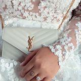 """Das Kleid aus dem Düsseldorfer Brautmodengeschäft """"IamYours"""" verzaubert mit durchsichtigen Einsätzen, die von vielen kleinen, weißen Blüten geziert werden. Dazu kombiniert sie eine kleine weiße Tasche von Saint Laurent."""