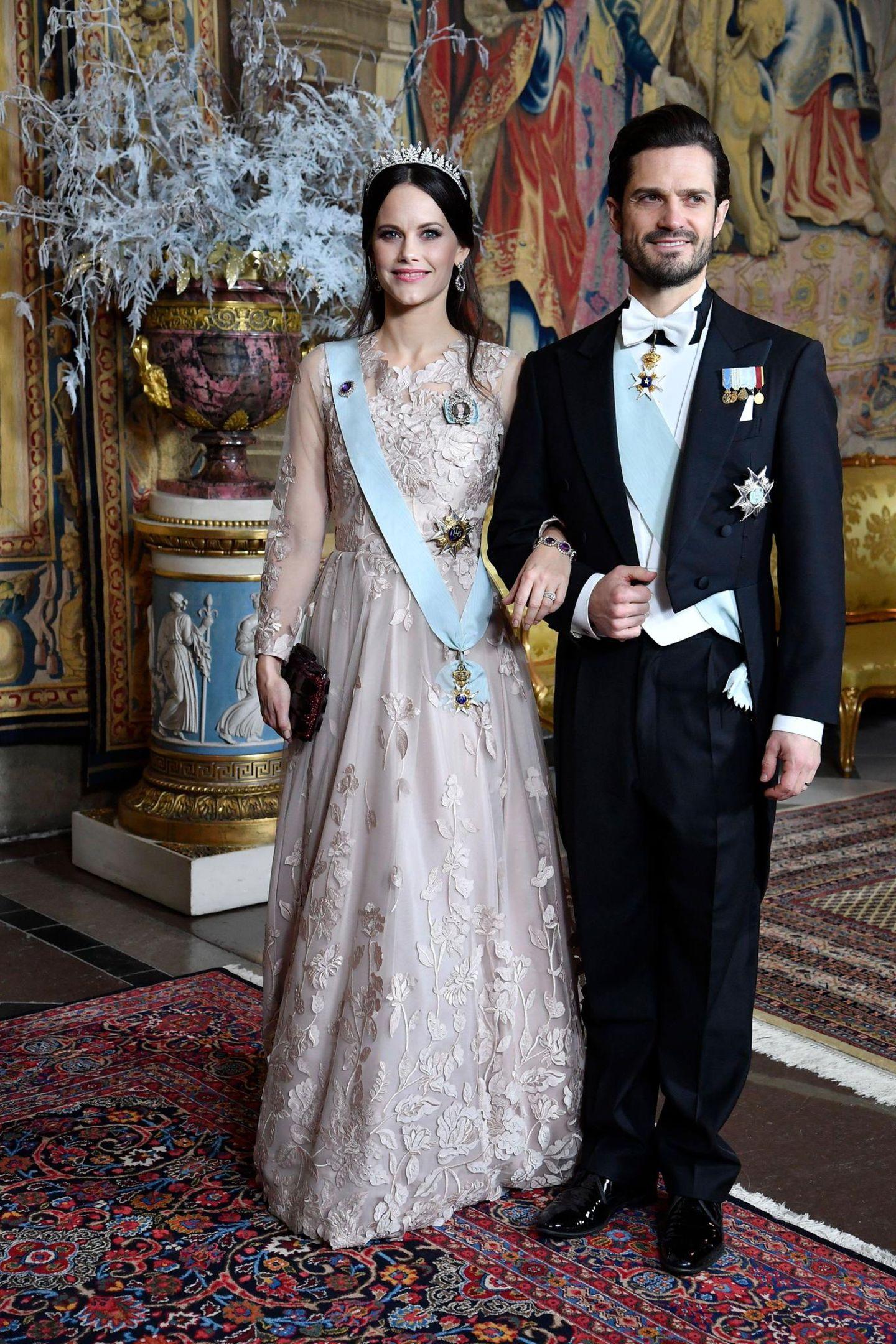 Beim Königsdinner zu Ehren der Nobelpreisträger im Schloss zeigt sich Prinzessin Sofia in einer blassrosa Traumrobe mit Blütenstickereien. Ihr dunkelbraunes Haar trägt sie halb hochgesteckt.