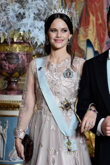 Das Kleid besticht durch transparente Ärmel. Dazu trägt die Prinzessin hängende Ohrringe und eine Tiara. Während sie am Vorabend in einem knallroten, engen Kleid begeisterte, gleicht sie beim heutigen Dinner einer zarten Elfe.