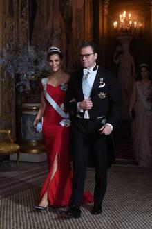 Als sie am Arm von Prinz Daniel zum Essen schreitet, zeigt sie besonders viel Haut. Der Beinschlitz ihres Kleides gewährt tiefe Einblicke und zeigt ihre Metallic-Pumps.