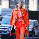 Denn auf einen BH verzichtet Gigi Hadid komplett und verleiht ihrem Look so einen sexy Touch. Um sich vor dem kalten Wind der Metropole zu schützen, hüllt sich das Model in einen orangefarbenen Ledermantel, der perfekt zu ihrem Outfit passt.