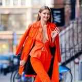 In knalligem Orange macht Gigi Hadid die Straßen New Yorks unsicher. Und das in einem Look, den wohl nur ein Supermodel ausführen würde: Zu einer Schlaghose mit bestickten Ornamenten kombiniert sie eine gleichfarbige Bluse, die nur mit einem Knopf in der Taille zusammengehalten wird – und lässt tief Blicken ...