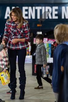 In Begleitung des Weihnachtsmanns verteilt Melania Trump in Washington Geschenke an bedürftige Kinder. In einer karierten Jacke aus der Feder des deutschen Designers Tomas Maier und einer engen, schwarzen Hose begrüßt sie die Kleinen.