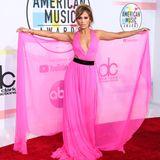 Auf dem Roten Teppich bei den American Music Awards erscheint JLo in einem pinken Maxikleid mit sexy Cut-Outs.Jimmy Choo-Accessoiresund eine schicke Hochsteckfrisur komplettieren den farbenfrohen Look.