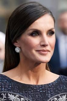 IhrsleekesHaar legt Königin Letizia streng nach hinten zurück, sodass man ihre funkelnden Ohrringe besonders gut sehen kann. Auch ihre Konturen - vor allem ihreWangenknochen - werden so und durch einen Hauch Bronzerhervorgehoben.