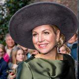 Zu ihren rosigen Wangen trägt Königin Máxima einen leicht pinken Lippenstift auf. Ihre Chignon knotet sie so, dass er schräg unter ihren Hut passt.
