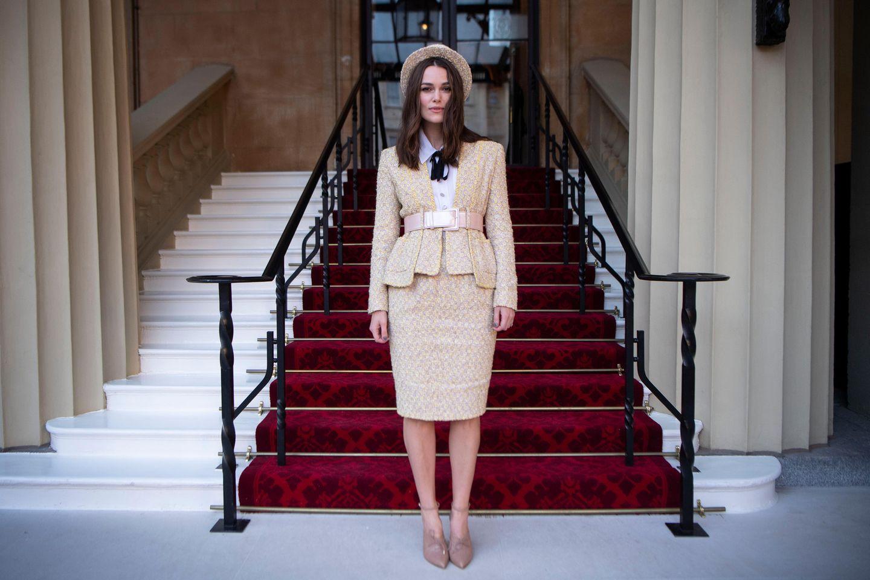 In einem creme-farbenen Chanel-Kostüm mit Hut und Schleife macht sie eine besonders adrette Figur. Sie scheint den Dresscode ernster genommen zu haben als ihre Begleitung...
