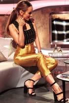 Dieser Look ist wahrlich Gold wert! Annemarie Carpendale weiß, wie man sich festlich und trotzdem sexy stylt, und präsentiert sich in einer goldenen Highwaist-Hose mit schwarzen Stilettos und einem schwarzen mit Perlen besetzten Top. Damit ist die schöne Moderatorin garantiert der Star auf jeder Party!