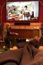 """Ein großer Flachbildfernseher, eine """"ganz bestimmt"""" hochwertige Soundanlage, kleinJameson an der Kindergitarre und dieweihnachtliche Wanddekoration machen aus Pinks und Carey Harts Wohnzimmer ein Paradies für Faulenzer. Die Socken gehören übrigens Papa Carey, der das Haus hütet, da beide Kids ihre Erkältung auskurieren."""