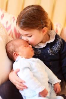Prinzessin Charlottes Strickjacke gehörte vorher nämlich ihrem großen Bruder. Zum 90. Geburtstag von Queen Elizabeth am 21. April 2016 veröffentlichte der Palast ein Porträt der Monarchin, umringt von ihren beiden damals jüngsten Enkelkinder und fünf Ur-Enkeln. Prinz George trägt auf diesem Bild die blaue Strickjacke. Eine schöne Tradition, Kinderkleidung für jüngere Geschwister aufzubewahren. Besonders royale Familien legen viel Wert auf diesen Kleidertausch.