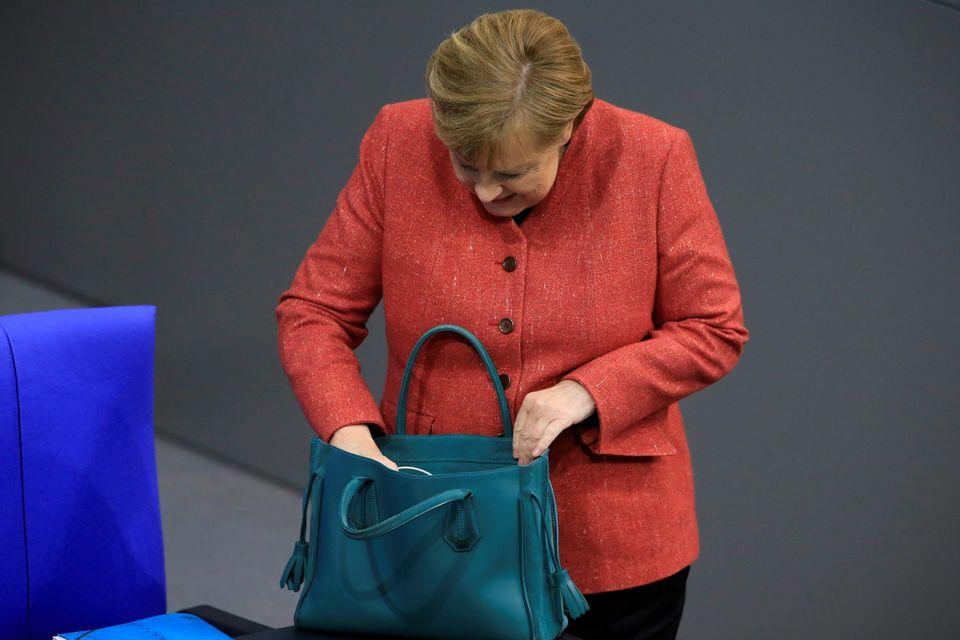 Bevor die Sitzung beginnt, holtAngela Merkel noch ihre Akten aus ihrer Handtasche. Was da wohl noch alles drin ist?! Außer einem Ladekabel fürs Smartphone läst sich das leider nicht erkennen.