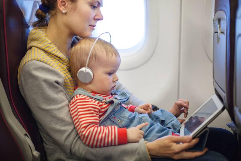 Eine Mutter fliegt mit ihrem Kleinkind