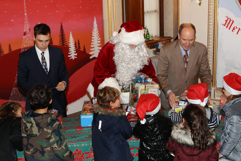 19. Dezember 2018  Gemeinsam mit dem Weihnachtsmann verteilenLouis Ducruet und Fürst Albert Geschenke beim Weihnachtsfest für die Kinder der Angestellten des Palastes in Monaco.