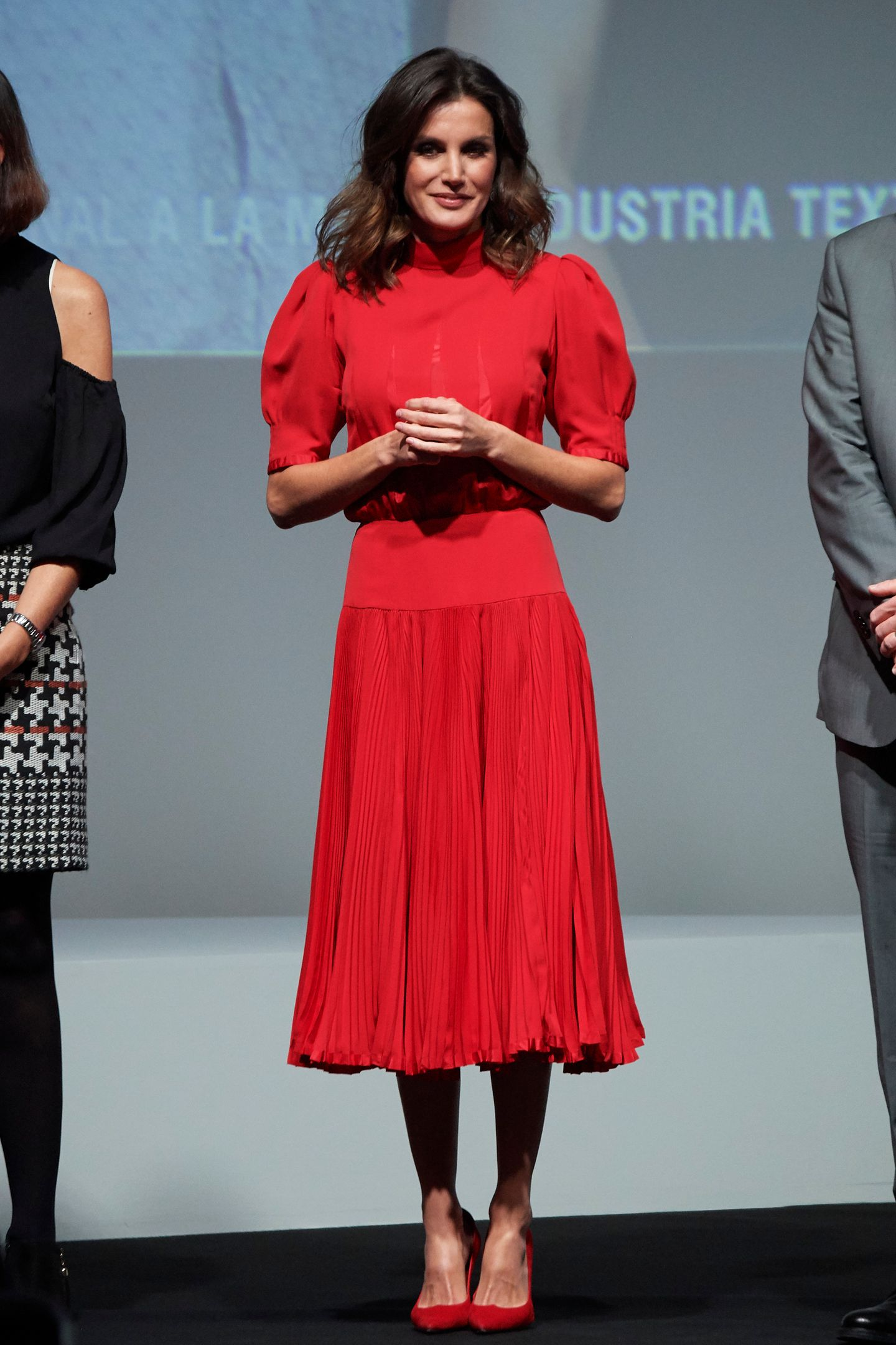 """Königin Letizia zeigt sich bei der Verleihung der """"National Fashion Awards"""" in Madrid in einem knallroten Dress. Es ist hochgeschlossen, in Midilänge und an der Taille eng geschnitten und erinnert stark an das Kleid, in dem sich eine andere Prinzessin erst Anfang der Woche zeigte..."""