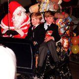 1990  Prinz William und Prinz Harry sitzen neben dem Weihnachtsmann auf einem mit Geschenken vollgepackten Schlitten.