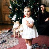 1978  Die etwa anderthalbjährige Kronprinzessin Victoria trägt an Weihnachten ein weißes Kleidchen und schaut mit großen Augen und mit ihrem Stoffteddy in der Hand in dieKamera. Mama Königin Silvia freut sich im Hintergrund über ihre süße Tochter.