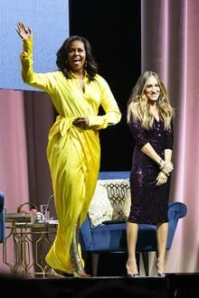 """Im Rahmen ihrer Buchtour spricht Michelle Obama mit Schauspielerin Sarah Jessica Parker in New York über ihr Buch """"Becoming"""". Bei diesem Auftritt sticht nichtnur ihr gelbes Wickelkleid direkt ins Auge. Die glitzernden Overknees der ehemaligen First Lady müssen Sie sehen..."""