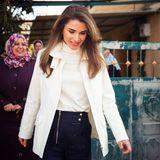 Königin Rania liebt Outfits mit dem gewissen Etwas: Beim Besuch des Dorfes Wadi Al Naqa kombiniert sie zu einem weißen Rollkragen-Pullover eine ebenfalls weiße Jacke und eine Hose, die mit raffinierten Knöpfe und einem langen Reißverschluss besticht.